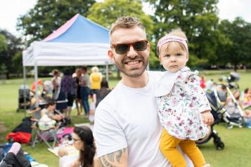 Man stood outside holding a young child