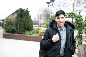 Male stood outside holding his bag