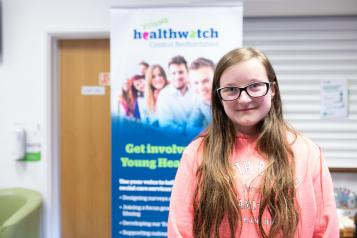 Young girl stood in a pink hoodie in front of a Healthwatch banner