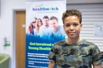 Young boy stood in front of a Healthwatch banner