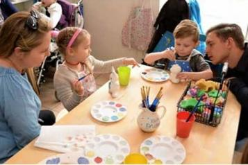Family sat around a table doing a craft activity
